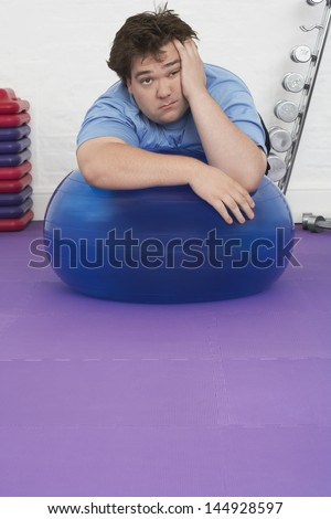 Portrait of a tired overweight man resting on exercise ball in health club - stock photo