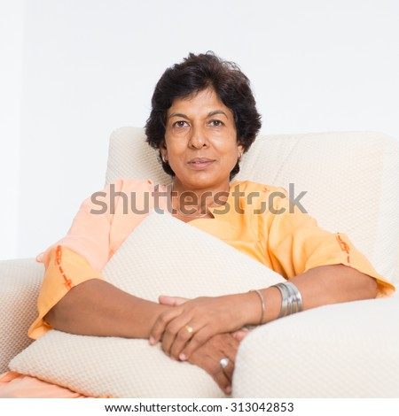 Portrait of a tired 50s Indian mature woman resting on sofa at home. Indoor senior people living lifestyle. - stock photo