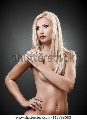 Portrait of a topless blond woman holding hand on shoulder - stock photo