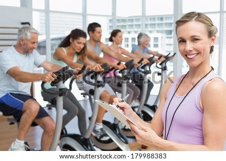Portrait of a trainer with people working out at exercise class in gym - stock photo