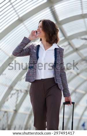 Portrait of a traveling business woman walking and talking on mobile phone - stock photo