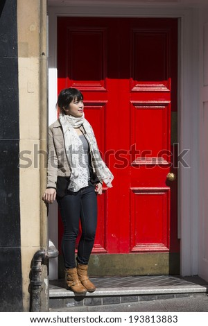 Portrait of a trendy Chinese woman standing by a red door. business or lifestyle image. - stock photo