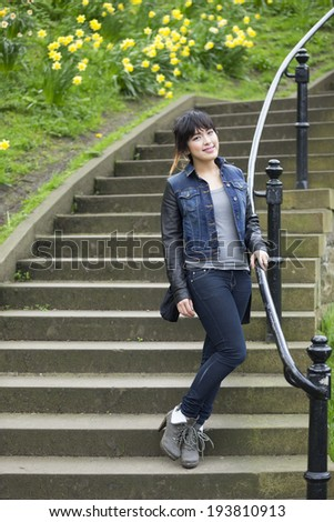 Portrait of a trendy Chinese Woman standing outdoors. Lifestyle image. - stock photo