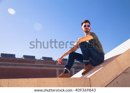 Portrait of a trendy young man on a sunny day in the city - stock photo