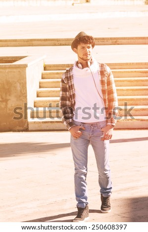 portrait of a trendy young man walking in the street applied filter instagram style and a flare effect - stock photo
