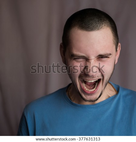 Portrait of a twenty-year-old man in a blue shirt and plaid shirt with natural light with flash on a white background, screaming man, feelings of anger, rage, hatred, a man in a rage - stock photo