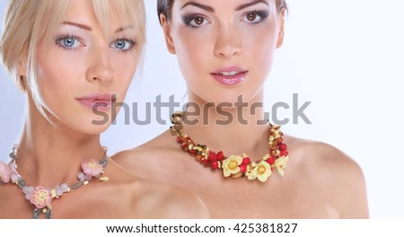 Portrait of a two beautiful women with necklace, isolated on white background - stock photo