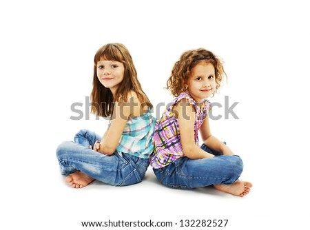 Portrait of a two little girls sitting back to back and smiling. Isolated on white background - stock photo