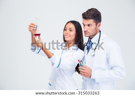 Portrait of a two medical workers looking at tube with liquid isolated on a white background - stock photo