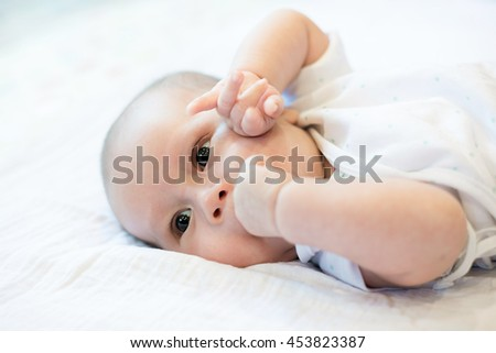 Portrait of a two month infant baby boy teething bites the hand sucking.Close up at infant baby. - stock photo