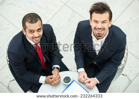 Portrait of a two young men during a business meeting, are looking at the camera. - stock photo