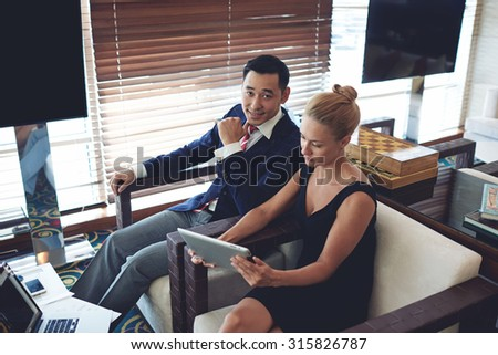 Portrait of a two young successful business people working together in office space, female secretary using digital tablet during work with her boss, men and woman entrepreneurs preparing for briefing - stock photo