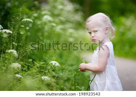Portrait of a very angry little girl outdoors - stock photo