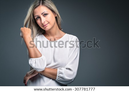 Portrait of a very attractive blonde, young woman on grey background, touching her lovely hair, looking both relaxed and confident (color toned image) - stock photo