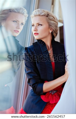 Portrait of a very beautiful sensual blonde girl in a black jacket and a red dress, looking into the distance through the glass with reflection - stock photo