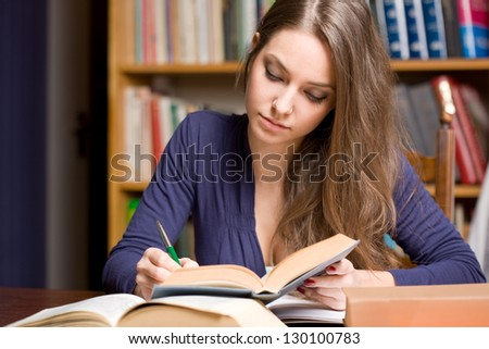 Portrait of a very busy young brunette student. - stock photo