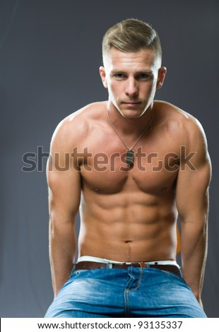Portrait of a very fit, ripped young man flexing muscles. - stock photo