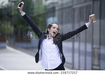 Portrait of a very happy caucasian businesswoman celebrating good news. Business woman with arms up in the air cheering. - stock photo