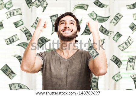 Portrait of a very happy young man in a rain of money - stock photo