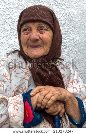 Portrait of a very lonely old woman with a worried and anxious expression, with deep wrinkles multiple  - stock photo