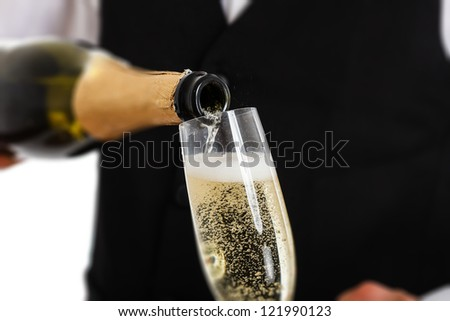 Portrait of a waiter pouring champagne into a flute - stock photo