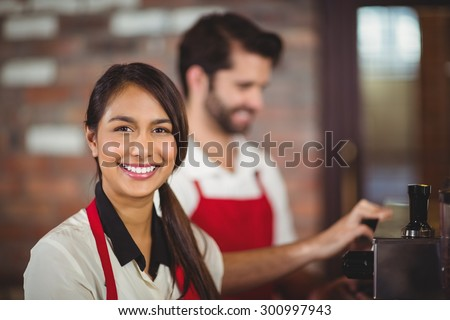 Portrait of a waitress using the coffee machine at the coffee shop - stock photo