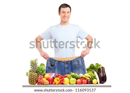 Portrait of a weight loss male showing his old jeans isolated on white - stock photo