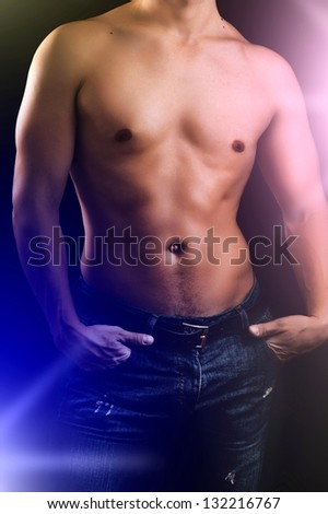 Portrait of a well built muscular man model against black background in studio - stock photo