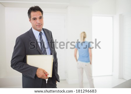 Portrait of a well dressed real estate agent with blurred woman in the background - stock photo