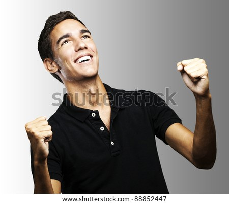 portrait of a winner young man looking up over grey background - stock photo