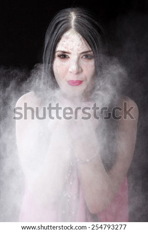 Portrait of a woman blowing a white powder over black background - stock photo