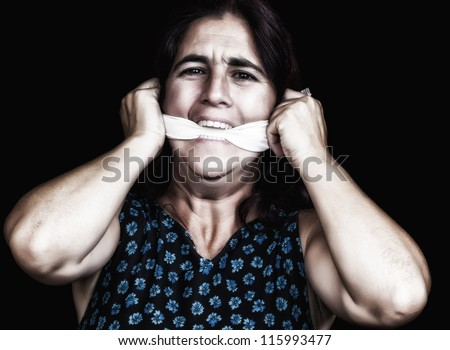 Portrait of a woman covering her mouth with a handkerchief to avoid talking isolated on black (useful to illustrate gender violence or discrimination) - stock photo