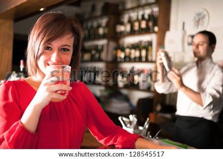 Portrait of a woman drinking a cocktail - stock photo