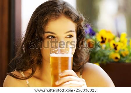 Portrait of a woman drinking beer in bar. - stock photo