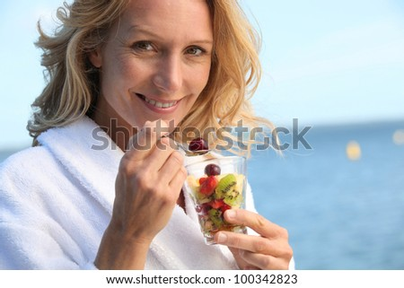 portrait of a woman eating fruit salad - stock photo