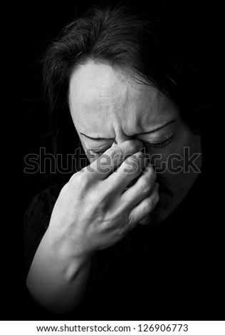 portrait of a woman feeling pain, frowning with hand on head with black background - stock photo