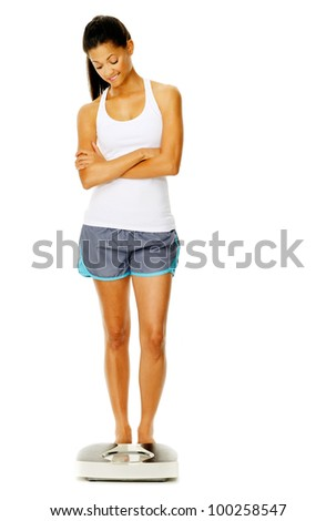 portrait of a woman full length with scale. unsure of whether to weigh herself or not. - stock photo
