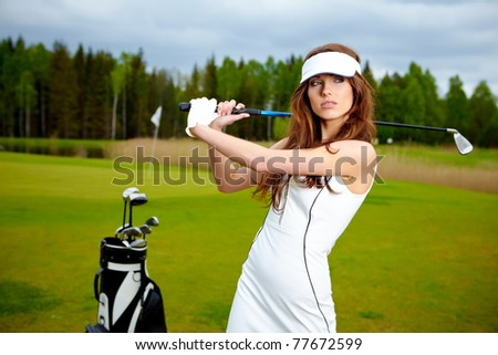 Portrait of a woman holding a golf club in her hands on a green - stock photo