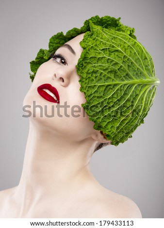 Portrait of a woman illustrating a vegan concept with a cabbage on the head - stock photo