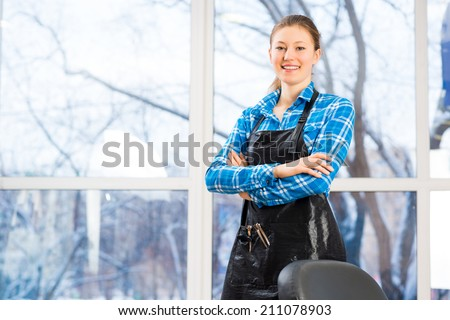 portrait of a woman in a barber shop barber worth apron crossed her arms - stock photo