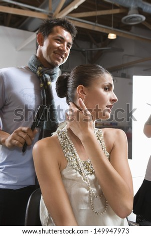 Portrait of a woman in dressing room with male hair stylist - stock photo