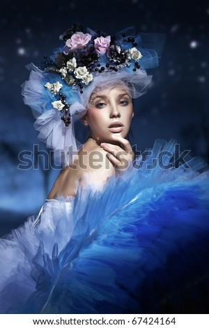 Portrait of a woman in hat made of flowers - stock photo