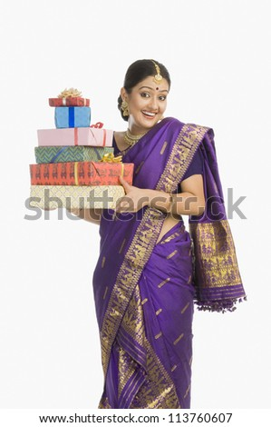 Portrait of a woman in traditional Assamese dress holding gifts and smiling - stock photo