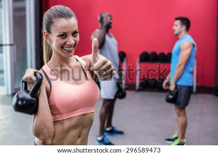 Portrait of a woman lifting a kettlebell and gesturing thumbs up - stock photo