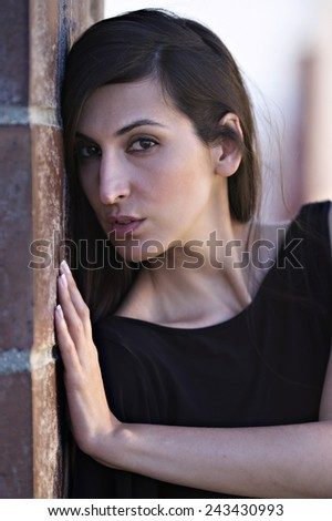 Portrait of a woman looking at camera, leaning against a pillar - stock photo