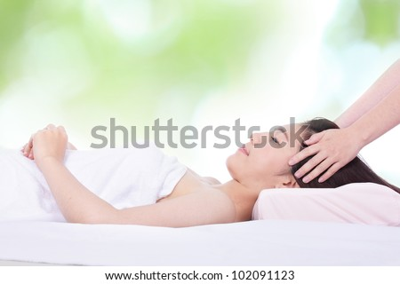 Portrait of a woman lying on a massage table in a health spa with nature green background, model is a asian girl - stock photo