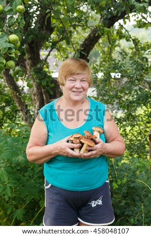 Portrait of a woman over 60 with mushrooms - stock photo