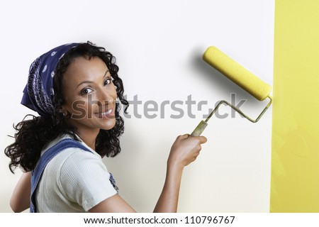 Portrait of a woman painting wall with paint roller - stock photo