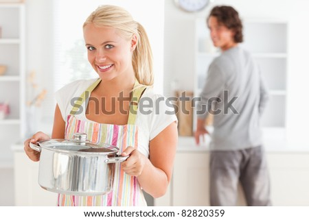 Portrait of a woman posing while a man is washing the dishes in their kitchen - stock photo