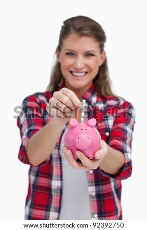 Portrait of a woman putting a note a piggy bank against a white background - stock photo